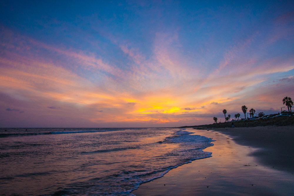 Bold blue and orange colors mark sunset on a tropical ocean beach.