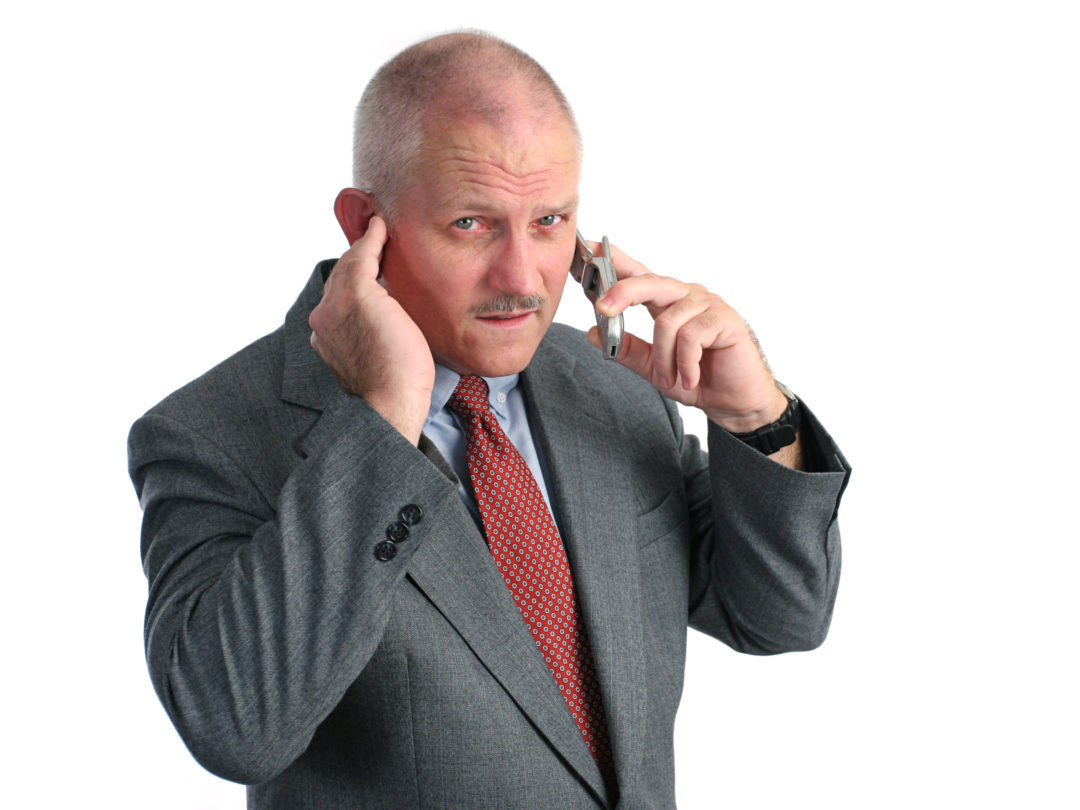 a man trying to hear his cellphone in a loud place - he looks annoyed
